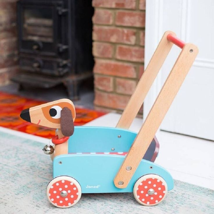 Wooden Dog Personalised Walker  A lovely dog walker great for getting little ones up on their feet. The wheels have rubber rings on them that won't mark the floor. The bell on the dogs neck rings as the walker is pushed along.  Made from solid wood and metal axles with cute little felt doggy ears.