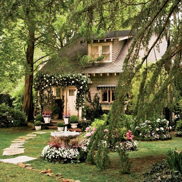 Cottage landscaping ideas from a film set: climbing roses arched over porch opening. Architectural Digest