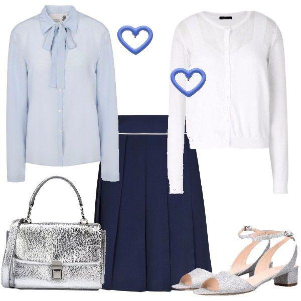 Gonna blu al ginocchio, modello a pieghe, camicia in seta azzurra con collo con fiocco, cardigan bianco con scollo tondo. Sandalo con glitter argento e tacco quadrato basso, borsa a tracolla effetto laminato.