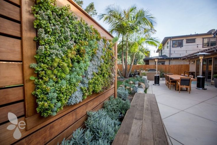 backyard with lounge area, grey flooring, plants box, and living green wall