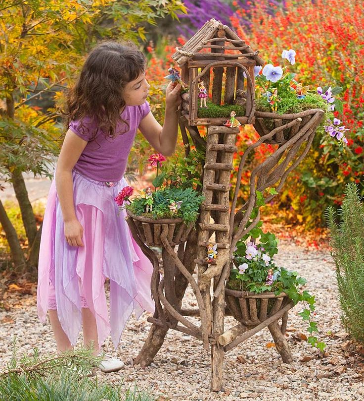 This has got to top it for me.  What is a plant stand becomes a house for little garden elves and faeries.