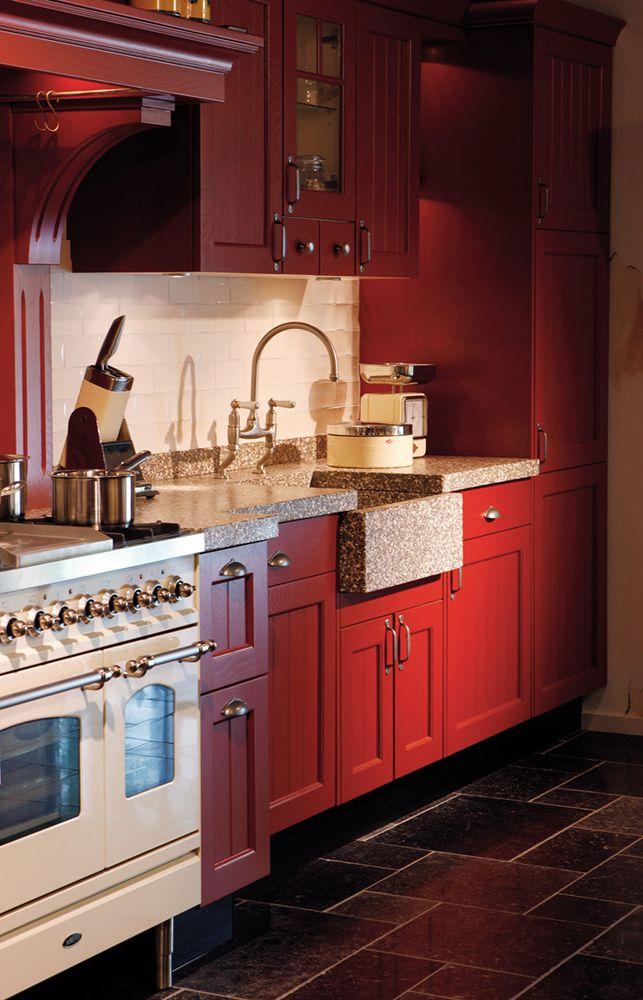 Sfeervolle landelijk rode keuken met authentiek terrazzo blad en creme boretti fornuis