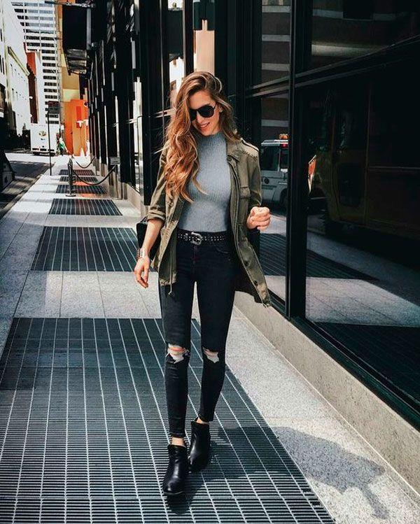 Look de inverno com jeans destroyed, bota preta, blusa cinza e parka militar.
