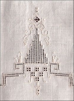 Linen towel with drawn thread work accented with embroidery in stem and satin stitch.