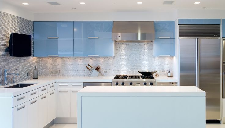 The patterned tile and blue glass finishes in the kitchen create a space that is both refined and visually striking.