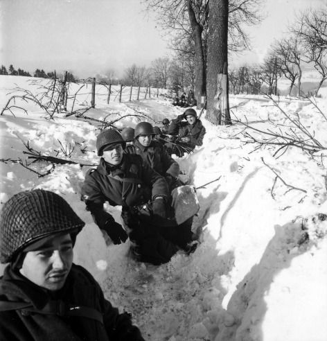 Amercian soldiers in a snowy ditch in Belgium during the Battle of the Bulge.