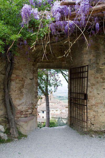 Muur met ijzeren hek met blauwe regen en doorkijk op dorpje