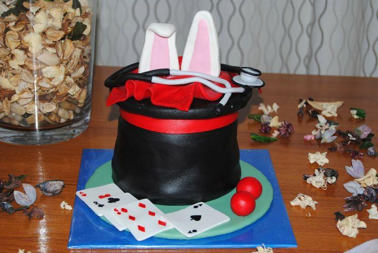 Tarta en forma de chistera con oreja de conejo, cartas de póquer, pelotas de goma y fonendoscopio.
