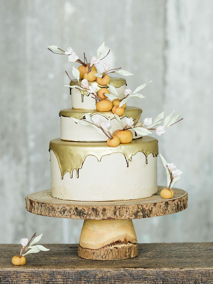 Drizzle a metallic gold drip around a staircase wedding cake for a trendy trim design. Fill in fruity fondant peaches around the tiers for a country-inspired contrast.