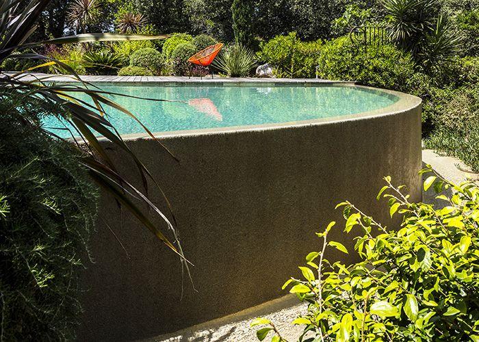L'eau ruisselle en silence sur le mur courbe, que viennent habiller rochers et plantes.
