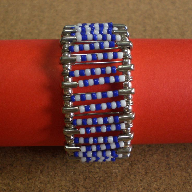 Another variant of bracelet made using safety pins with blue and white plastic beads. Connected with silver round beads.