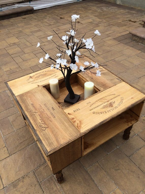This beautifully hand crafted coffee table is made from wine distribution boxes. Each has the wine label burned into the side. It is stained in a multi- color pattern of golden oak, summer oak and natural oak. The center top is removable to add an extra display cubby to your room . Each side has a storage area for your books/ remotes and more ! Table shown measures 32 X 32 X 20 This item is custom made to order. If you have a different size in mind. No problem! You dont like the labels a…