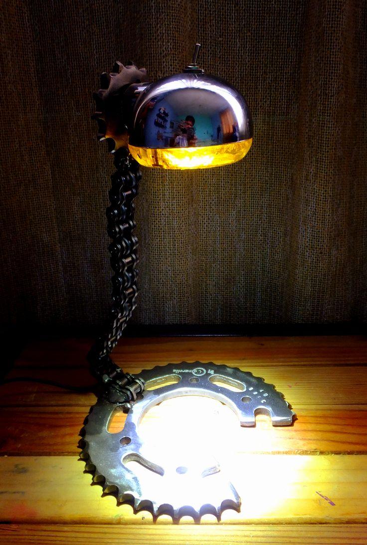 Lampara hecha con material reciclado, partes de moto, cadena engranajes y luz direccional. dimensiones 28cm de alto 18 cm ancho en la base Lamp made with recycled materials, motorcycle parts, chain, gears and directional light.
