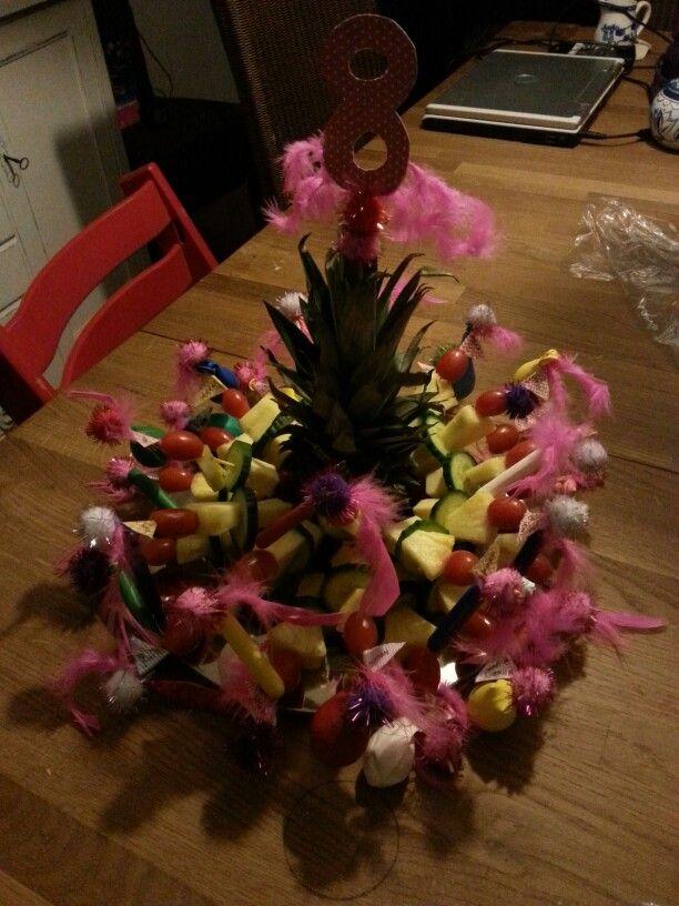 gezonde spiesjes versierd met veertjes, pompommen en ballonnen in een halve ananas gestoken