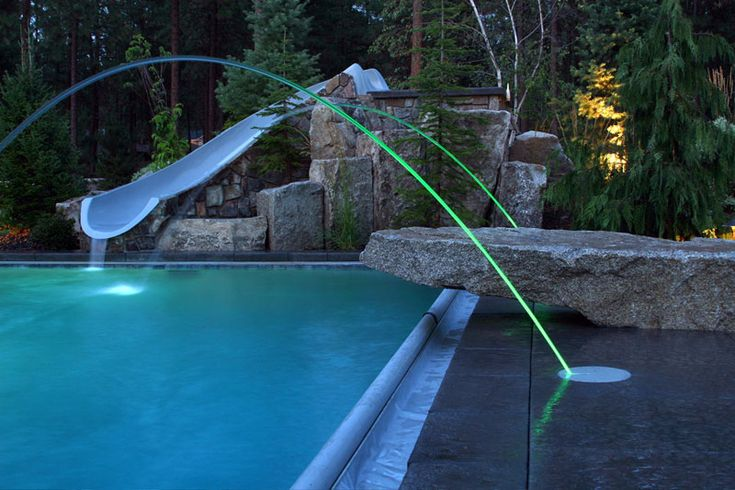 Led lit laminar jets adorn this pool surrounded by for Pool jets design
