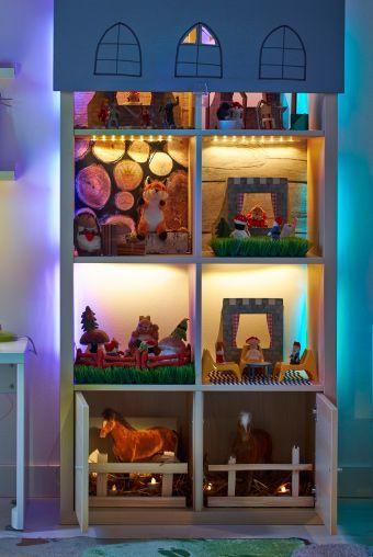 """""""Ein KALLAX Regal in Birkenachbildung, das zum Puppenhaus umfunktioniert wurde, mit vielen Stofftieren darin. LED-Lichtleisten beleuchten jedes einzelne Fach. Über dem oberen Teil hängt ein Rollo, in das Fenster geschnitten wurden. Links vom Regal steht ein Kinderschreibtisch mit Leuchte.:"""