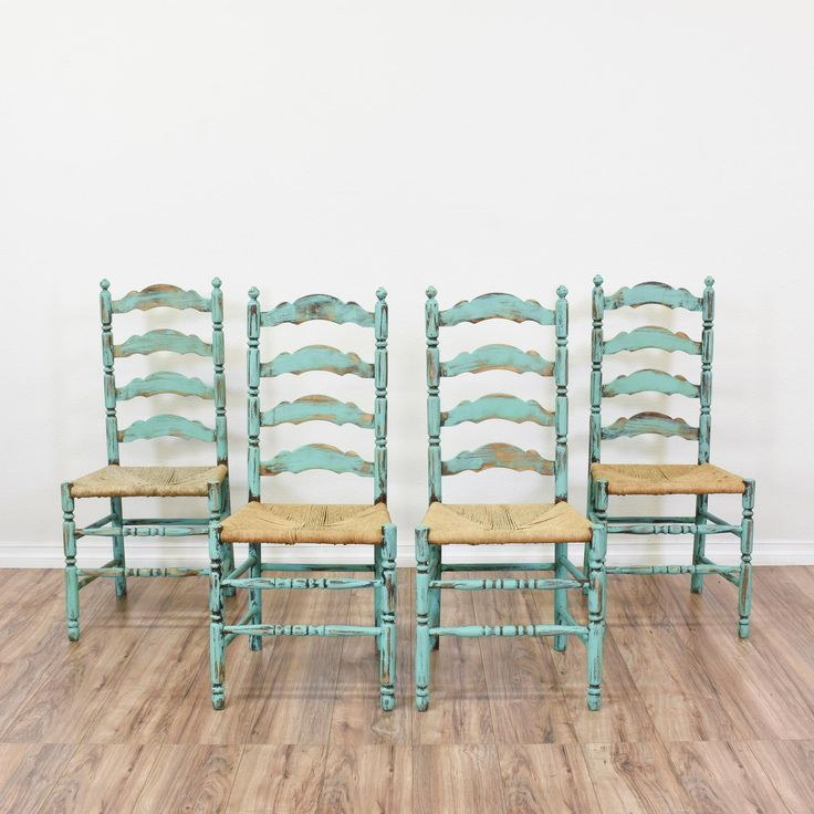 This set of 4 shabby chic ladder back chairs are featured in a solid wood with a distressed light blue chalk paint finish. These dining chairs are in great condition with tall ladder backs, carved spindle legs and woven wicker seats. Eclectic chairs perfect for casual dining in a breakfast nook! #shabbychic #chairs #diningchair #sandiegovintage #vintagefurniture