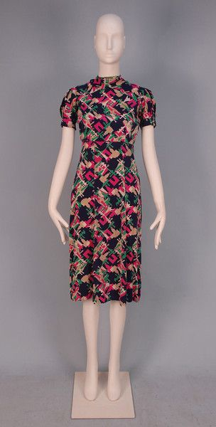 """* SCHIAPARELLI FABRIC DRESS, c. 1940. Homemade day dress sewn with Schiaparelli's printed silk """"Paris Exposition 1937"""" fabric depicting silhouettes of various landmarks including the Eiffel Tower and Arc de Triomphe in green, fuchsia, cream and ecru on navy ground, short puffed sleeve with crossed cut out neck band and back self button and loop closures"""