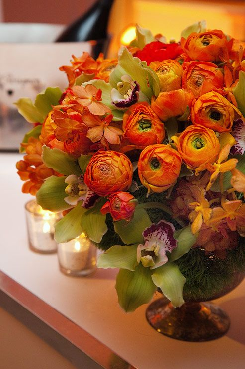 Bright orange ranunculi are accented with light green cymbidium orchids.
