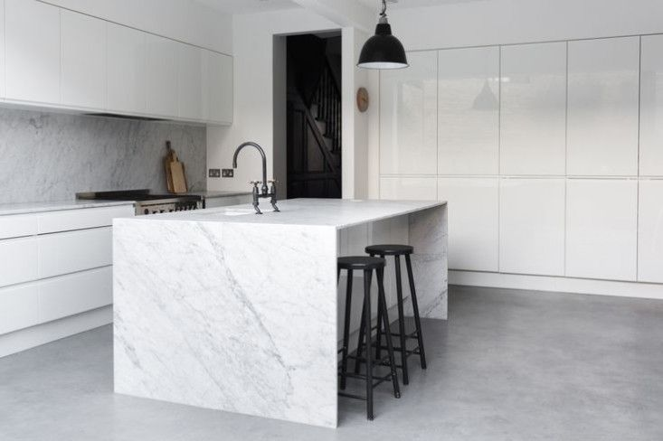 Kitchen: white handleless cabinets, pale grey and white marble splashback and benchtops, island with waterfall, grey polished concrete floor, black bar stools, black vintage industrial pendant lamp