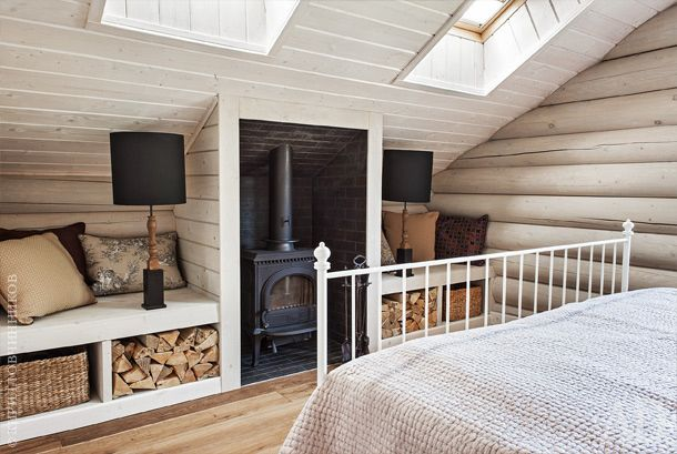Хозяйская спальня находится в мансарде. Под скосами крыши дизайнеры организовали встроенные лавки с отсеками для хранения дров.