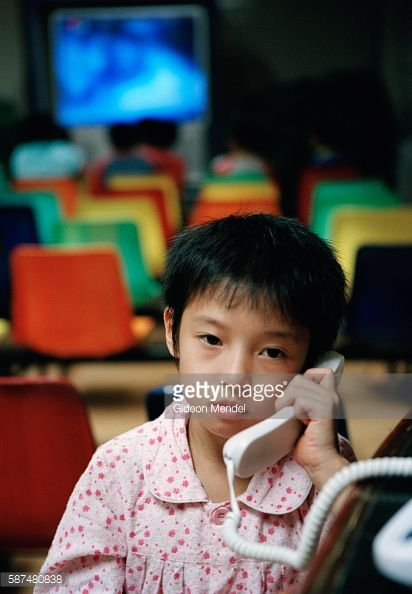 Young gymnast Niu Sizhuo (8) talks to her mother on the phone in the communal recreation area at the Shishahai Sports School. She is from Hebei Province and had not seen her family for a long time. Shishahai is one of the most successful training venues in China, where young gymnasts and other sports trainees live and start intensive training from the age of five.