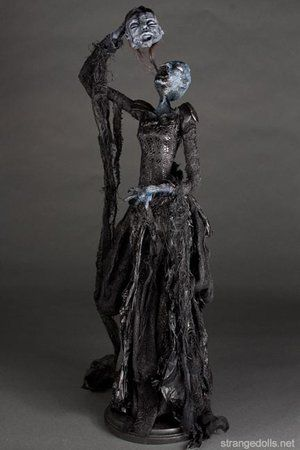 They stand 28 inches tall and are mounted to a wood base. The body is hand sculpted using a mixture of air dry clay. The clothing is fashioned from recycled materials: crab pincers, snail feet, chain, plaster, cheesecloth... and  Lord Gallow's hair. These Soul Eaters were made in 2014.
