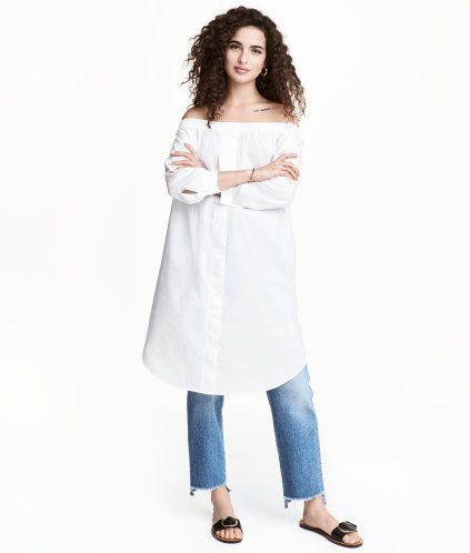 Weiß. Kurzes, schulterfreies  Kleid aus leichtem Baumwollstoff. Das Kleid hat oben einen Gummizug und lange Ärmel mit geknöpftem Schlitz unten. Abgerundeter