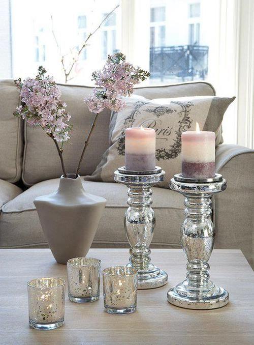 mesa de centro da sala de estar decorada com velas em tons de rosa e lilás, decoração cinza e prata