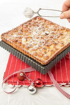 Dusting the Macadamia & Caramel Tart with icing sugar