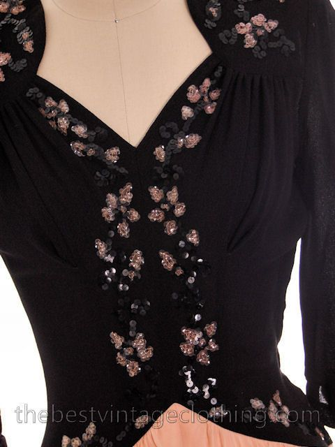 Lovely vintage 1940s evening gown of rayon with a pink and black floral sequinned motif on the bodice. It has a sweetheart neckline and a peaked waist and is lo
