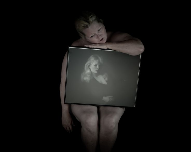 Picture of a woman holding an old photograph of herself
