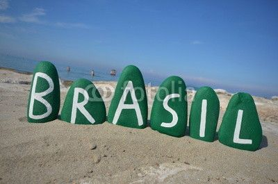 Brasil on green stones with beach background