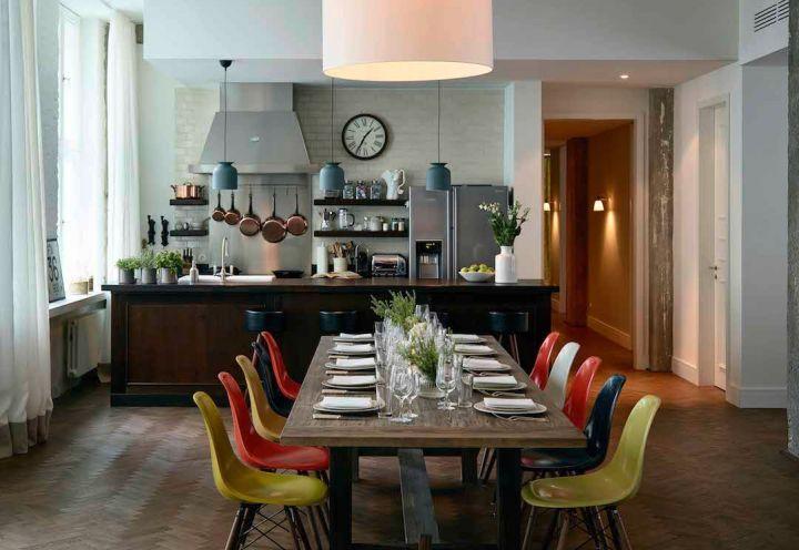 I loft della Soho House di Berlino sono tutti accessoriati. Cucina ad isola con tavolo da pranzo e sedie multicolor Vitra di Charles a Ray Eames
