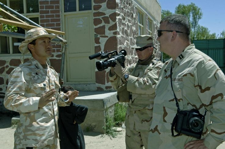 U.S. Air Force Staff Sgt. Leigh Bellinger, 2nd from right, from Armed Forces Network Afghanistan, videotapes Capt. Pwoungnook Moon, from the Korean Engineers Group, as he explains how the ceiling of the Aroki Boys School collapsed during class hours in the Kapi Si District, Afghanistan, June 20, 2006