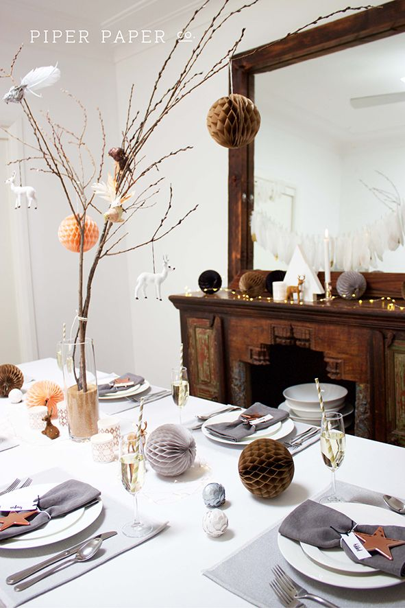 Piper Paper Co.'s Christmas Table Setting, Christmas Centerpiece and Christmas Mantle. A winter wonderland of reindeers, branches, birds, honeycomb balls, pinecones, candles, gold dipped feathers & of christmas string lights