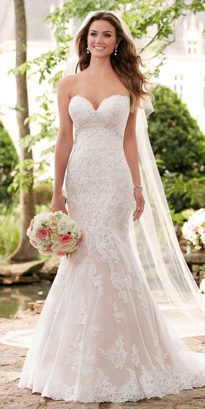 This romantic lace wedding dress by Stella York features a shimmery bead work and lace pairing that creates a soft hourglass shape. Linear lace on the bodice creates curves in the waist while a very subtle beaded empire waist draws attention to the bride's face. The lace details throughout the dress give brides a romantic and elegant feel that is accentuated by a strapless sweetheart neckline.