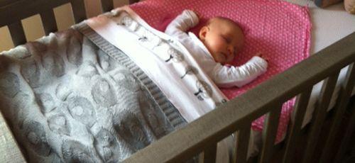Baby slaapt in rugligging. Bedje is kort opgemaakt (kan nog iets korter). Geen knuffels in bed. De doek onder baby's hoofdje zou nog weg kunnen.