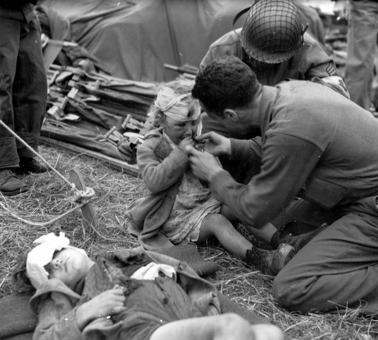 """War is full of tragedies. Two French children, Genevieve and Auguste Marie, are being treated by American medics after US bombers hit a German battery near their house in La Truncated killing their mother and wounding them both. Genevieve appears in """"better"""" shape than her brother, who's lying next to her, probably unconscious. This photo found its way to US newspapers on July 6, 1944."""