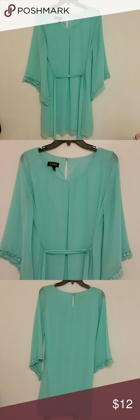 "A.Byer Dress Turquoise sheer bell sleeves dress will be an asset to any wardrobe. The sleeves has a lace type of trim and hangs perfectly, has a peep hole in the back with a button closure. This dress is so pretty has a pleat down the front and comes with a frabric belt. The color alone makes this dress stand out. The material is 100% polyester and so is the lining. The measurements ate 17"" across the chest and approximately 26"" from arm pit to hem. A.Byer Dresses Midi"
