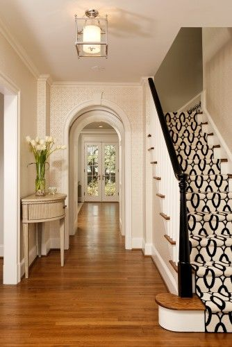 A foyer welcomes guests with a curved doorway & stylish carpet runner.