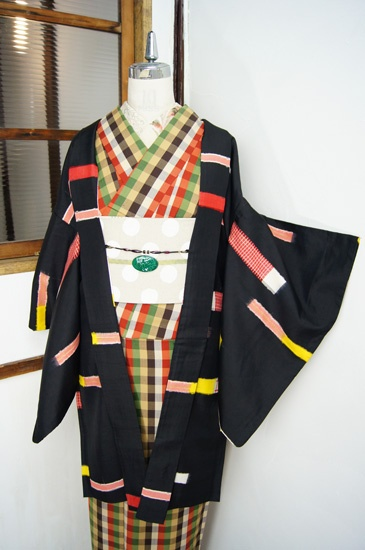 黒の地に赤白チェックや黄色で織り出された、マスキングテープでデコレーションしたようなボーダーデザインがレトロポップキュートな銘仙長羽織です。