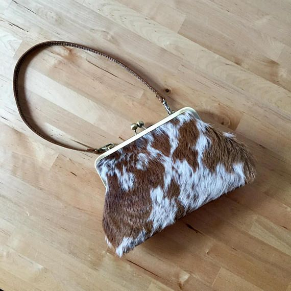 Brown and White cowhide clutch with strap. antique gold frame