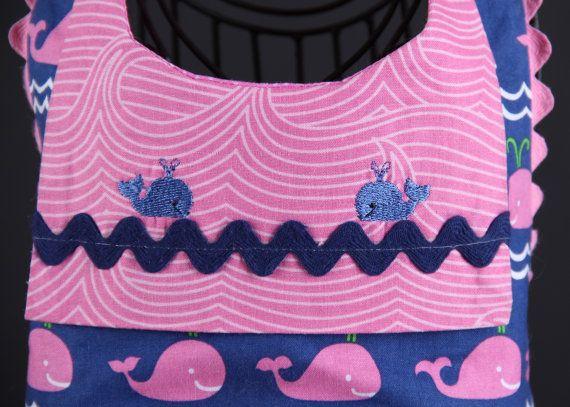 Este arnés es moda, funcional y sobre todo... divertido! Este arnés caprichosas características ballenas rosa sobre fondo azul marino mediano. Cada mazo está hecho a mano con calidad 100% algodón. El arnés tiene un anillo en D en la parte inferior del arnés (bajo el adorno de proa) y