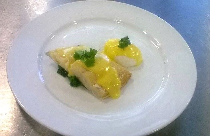 Poached smocked haddock served on a bed of spinach, poached egg with hollandaise and parsley to garnish