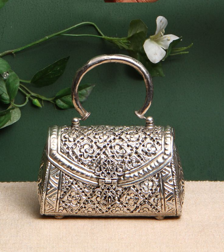 5 Elements By Radhika Gupta – Silver Metal Embossed Clutch Click on the photo to…