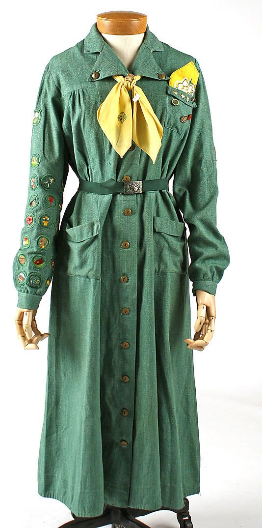 """Girl Scout's uniform designed by Mainbocher, American, ca. 1953. Green cotton dress and elastic belt with metal buckle, yellow neckerchief and yellow-edge floral handkerchief, worn with rust orange cotton velveteen beret. Label: """"Girl Scout's/Trademark GS/National Equipment Service/New York City/Official Uniform"""""""