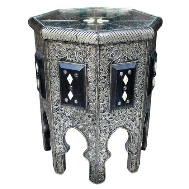 Meisterhaft und geschmacksvoll wurde dieser Orientalischer Tisch aus Massivem Holz gefertigt. Aufwendig wurde eine Silberschicht -Edelmetall/ Maychort- zur Verkleidung des Holzes filigran verarbeitet. Eine Dunkle Patina, die ungleichmäßig aufgetragen wird, gibt der Oberfläche den Perfekten Reliefeffekt. Zusätzlich verzieren Ornamente aus präparierten Knochen und Nieten die Oberfläsche.