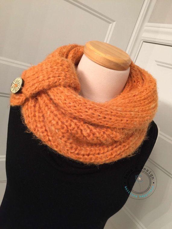 Très pratique, ce snood peut aussi se porter en capuchon pour les journées plus froides.  Une ganse amovible fermée par un gros bouton de bois lui apporte un look très élégant  Vous apprécierez sa souplesse, sa douceur et la chaleur quil vous procurera  Couleur: mandarine  Tricoté à la main dans un fil de qualité chaud et très doux  Composition: laine, nylon  Dimensions: 42 cm haut x 60 cm large  Lavage eau froide, cycle délicat Séchage à plat