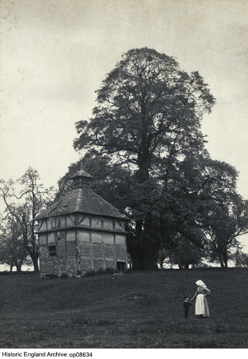 OP08634 View of a half-timbered dovecote at Oddingley, Worcestershire showing a woman and child standing in the foreground.  Please click for more information or to search our collections.
